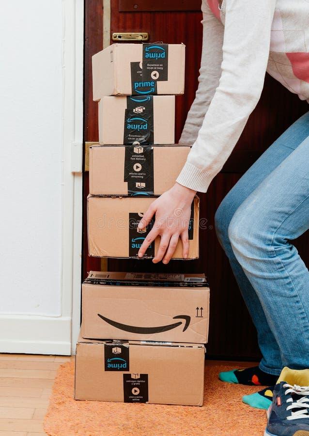 Pila de paquetes de la prima del Amazonas entregados a una mujer casera de la puerta imagenes de archivo