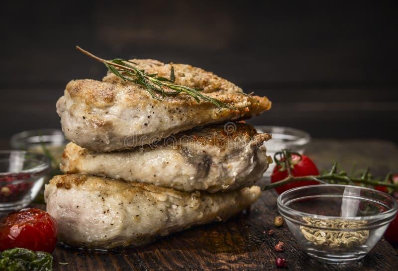 Pila de pecho de pollo asado con el condimento frito y de tomates en fondo de madera oscuro foto de archivo