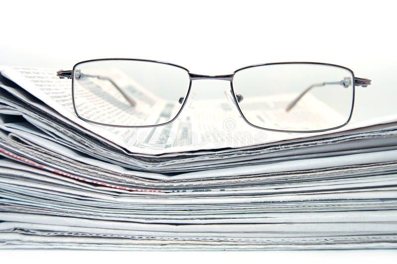 Pila de periódico con las lentes fotos de archivo