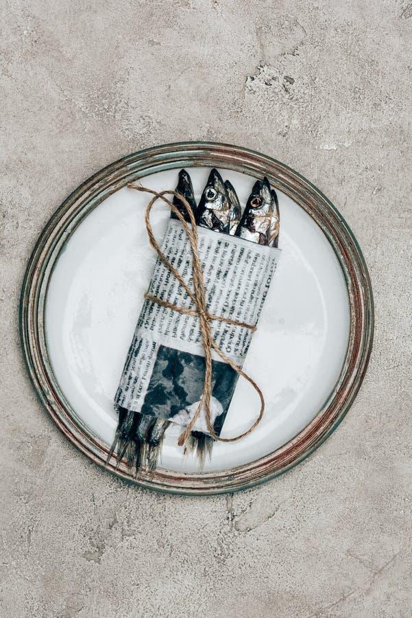 Pila de pescados en el periódico envuelto por la secuencia foto de archivo