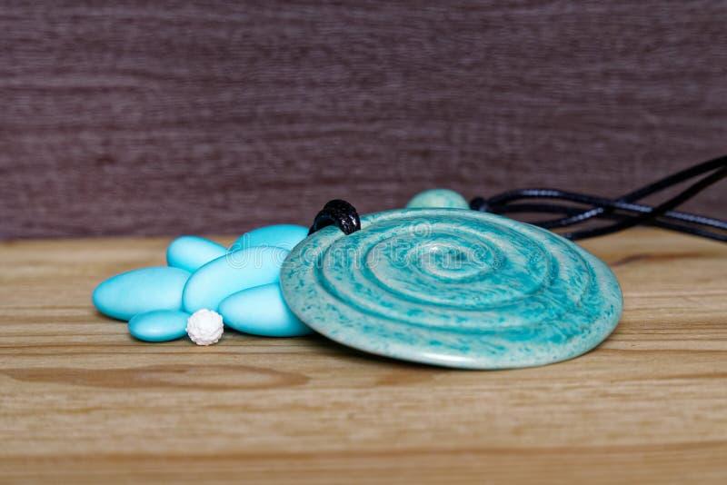 Pila de piedras azules con el amuleto decorativo en la tabla de madera, la muestra para la postal o la tarjeta de felicitación foto de archivo libre de regalías
