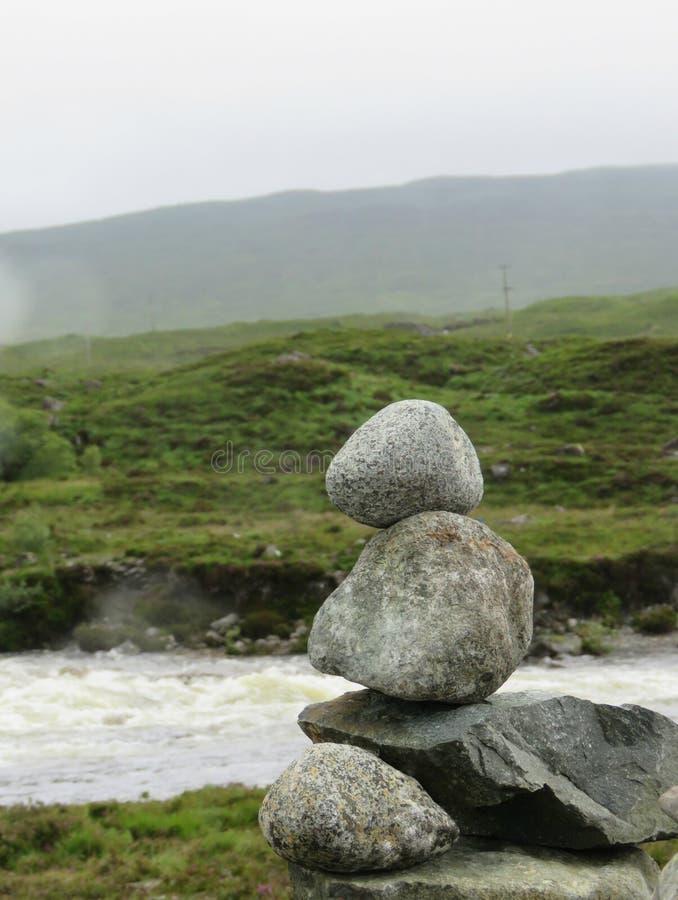 Pila de piedras con un fondo del río fotos de archivo