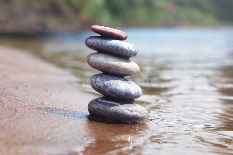 Pila de piedras de equilibrio del guijarro en el borde de la arena y del agua como símbolo del zen imágenes de archivo libres de regalías
