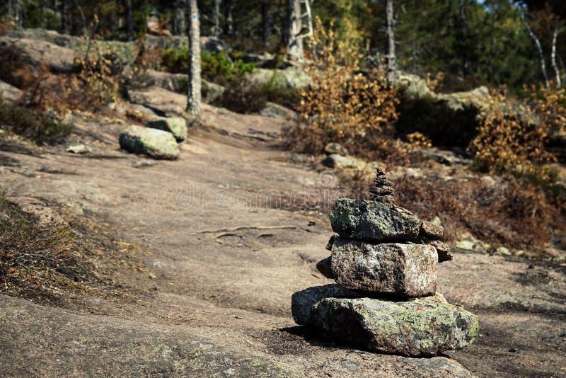 Pila de piedras que marcan la pista de senderismo en la montaña imagenes de archivo