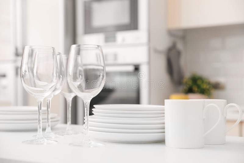 Pila de platos, de vidrios y de tazas limpios en la tabla imagenes de archivo