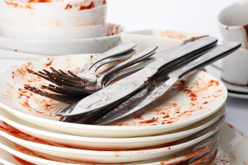 Pila de platos y de cubiertos sucios imagen de archivo