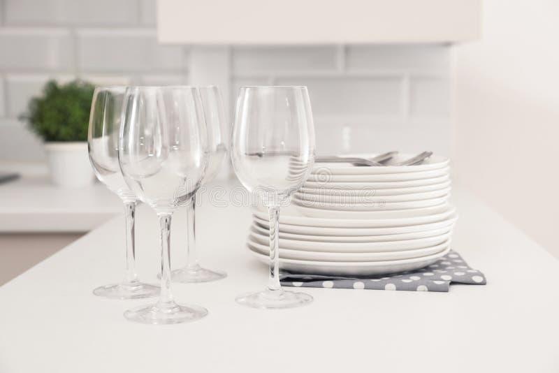 Pila de platos y de vidrios limpios en la tabla imagenes de archivo