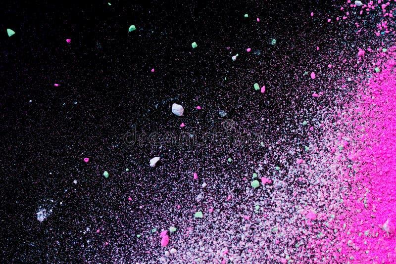Pila de polvo coloreado natural del pigmento Las part?culas blancas rosadas verdes del polvo salpican en blackground negro fotografía de archivo libre de regalías