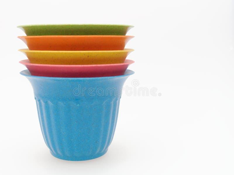 Pila de pote plástico de la planta del multicolor vacío con punteado y pelado en el fondo blanco imagen de archivo libre de regalías