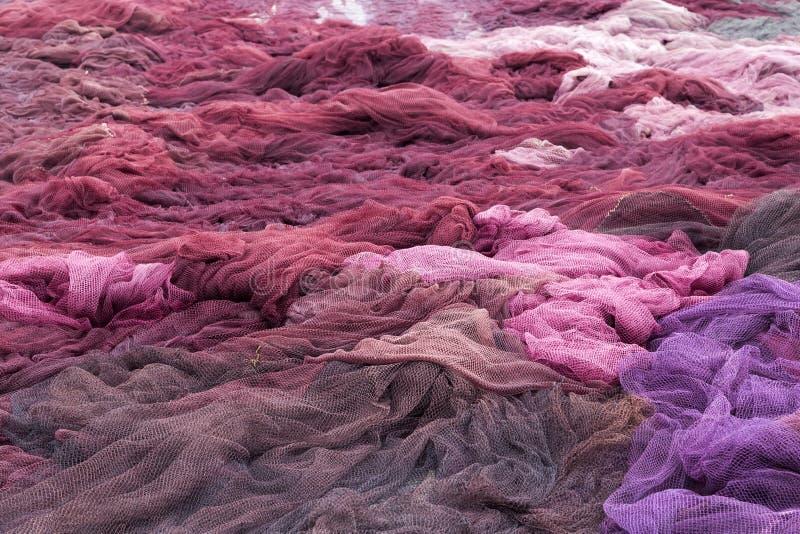 Pila de redes de pesca marrones, violetas y rosadas foto de archivo
