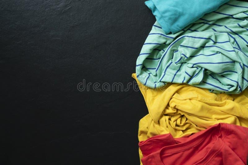 Pila de ropa colorida sucia mezclada lista para lavarse en el fondo del negro de la tabla imagen de archivo libre de regalías