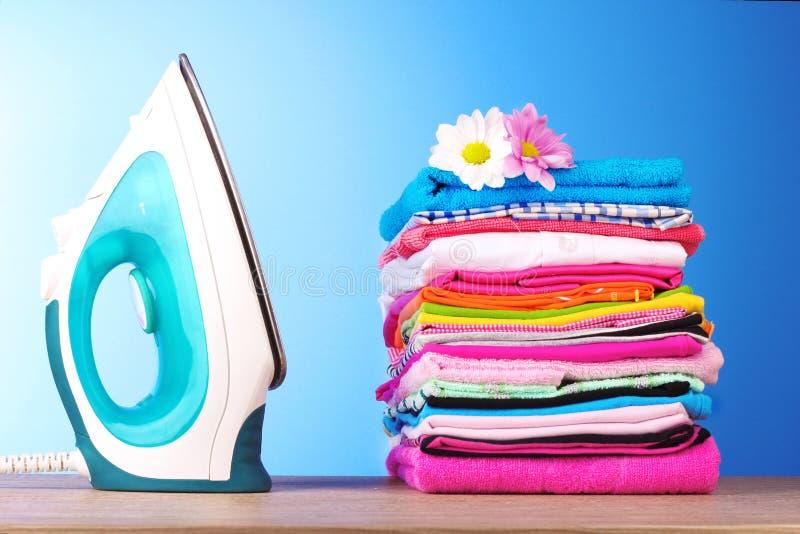 Pila de ropa colorida y de hierro eléctrico fotos de archivo libres de regalías