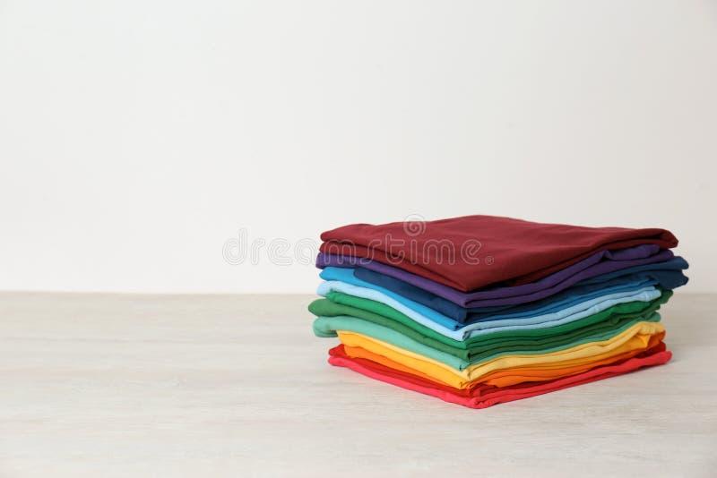 Pila de ropa doblada brillante en la tabla contra el fondo blanco fotografía de archivo