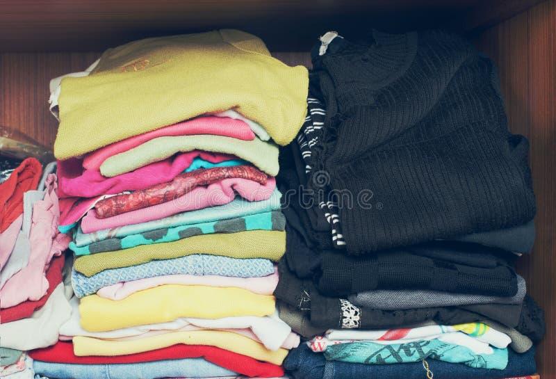 Pila de ropa de la camiseta en armario La pila de muchos color dobló las camisas de la mujer cubiertas imagenes de archivo