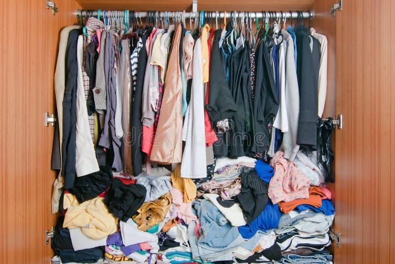 Pila de ropa sucia en armario Guardarropa estorbado desordenado de la mujer fotografía de archivo