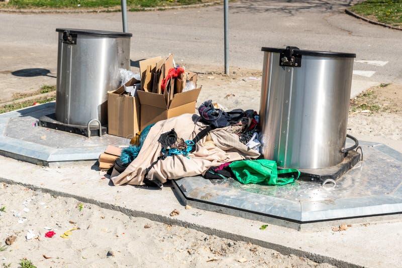 Pila de ropa vieja y de zapatos descargados en las latas subterráneos del contenedor como los desperdicios y basura, dejando en d fotografía de archivo libre de regalías