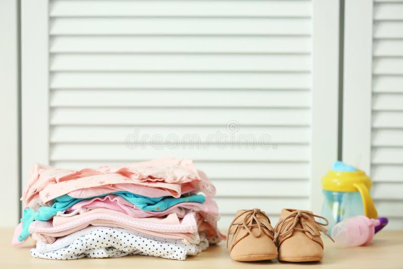 Pila de ropa y de zapatos del bebé foto de archivo