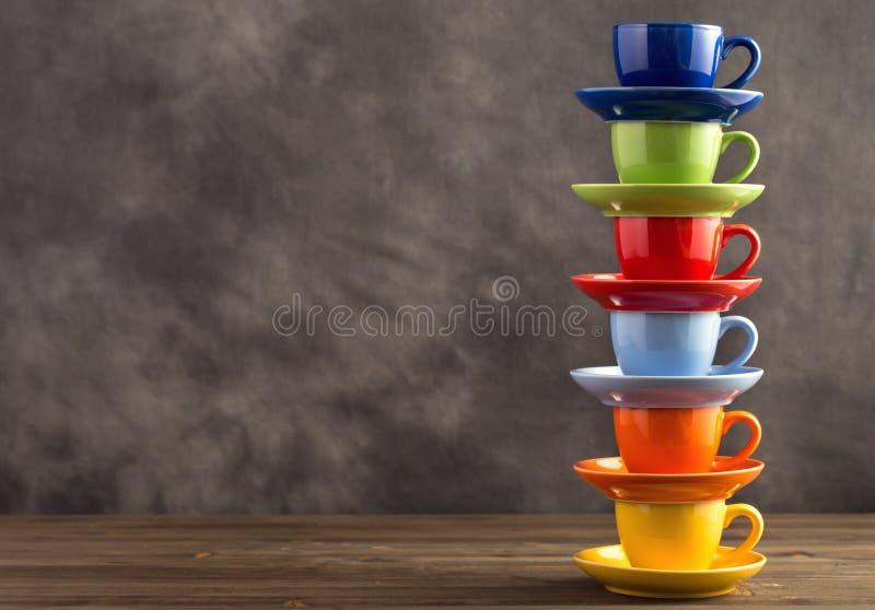 Pila de seis tazas multicoloras en la tabla del lado derecho imagenes de archivo