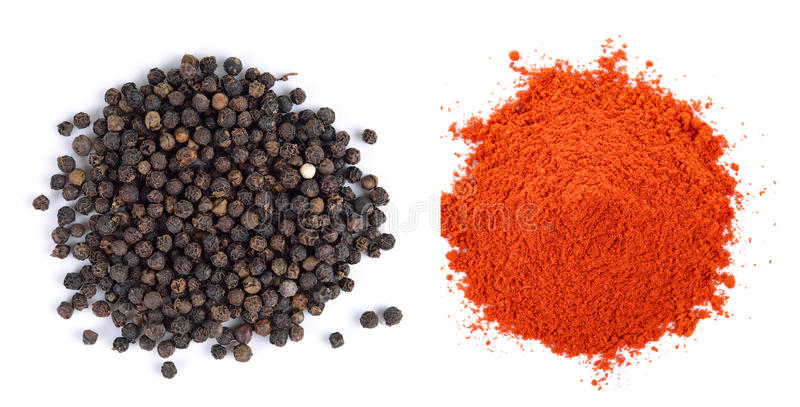 Pila de semillas del polvo rojo de la paprika y de la pimienta negra en el backg blanco foto de archivo libre de regalías
