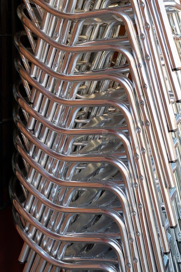 Pila de sillas de aluminio en un restaurante fotos de archivo