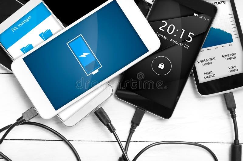 Pila de smartphones conectados con la fuente de energía fotografía de archivo libre de regalías