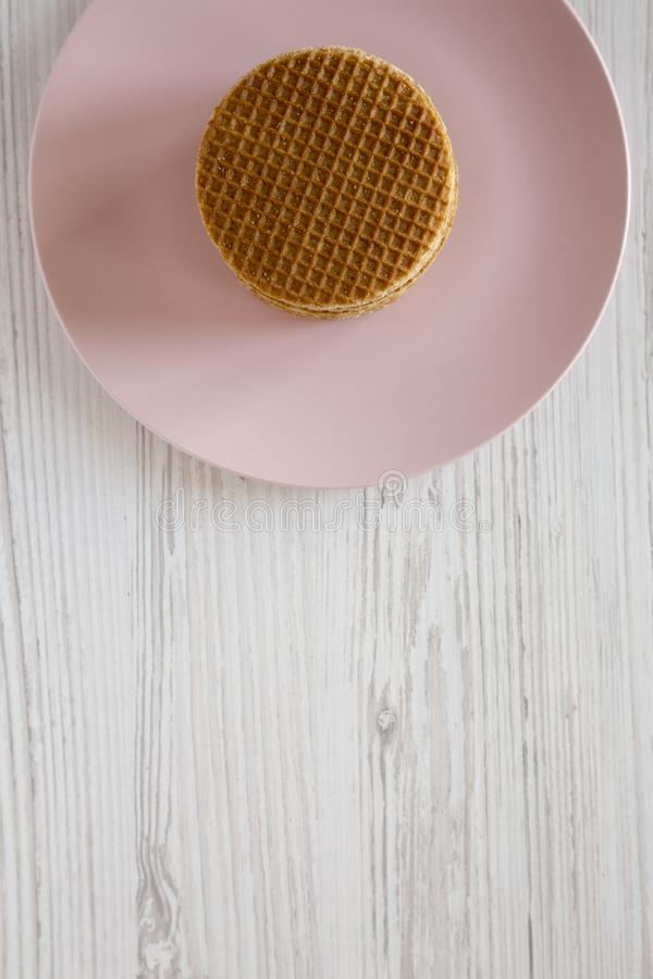 Pila de stroopwafels holandeses hechos en casa con el relleno del miel-caramelo en la placa rosada, visión desde arriba Copie el  fotos de archivo