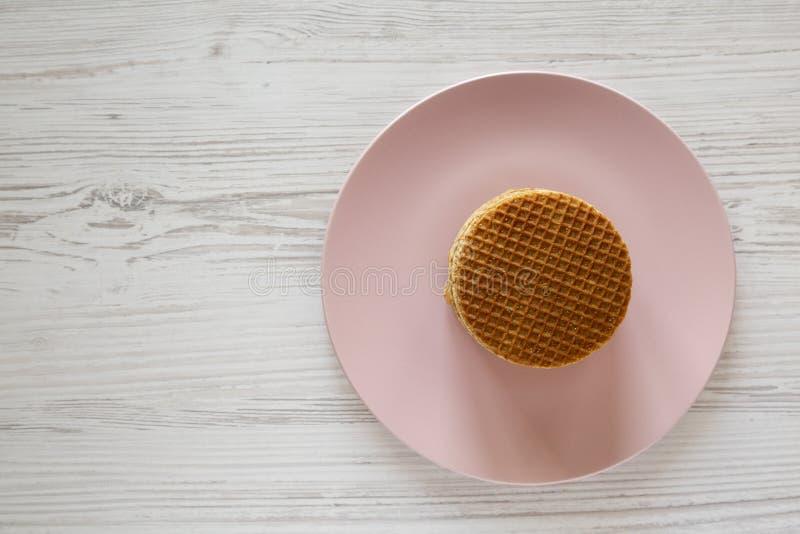 Pila de stroopwafels holandeses hechos en casa con el relleno en una placa rosada, visión de arriba del miel-caramelo Endecha pla fotografía de archivo libre de regalías