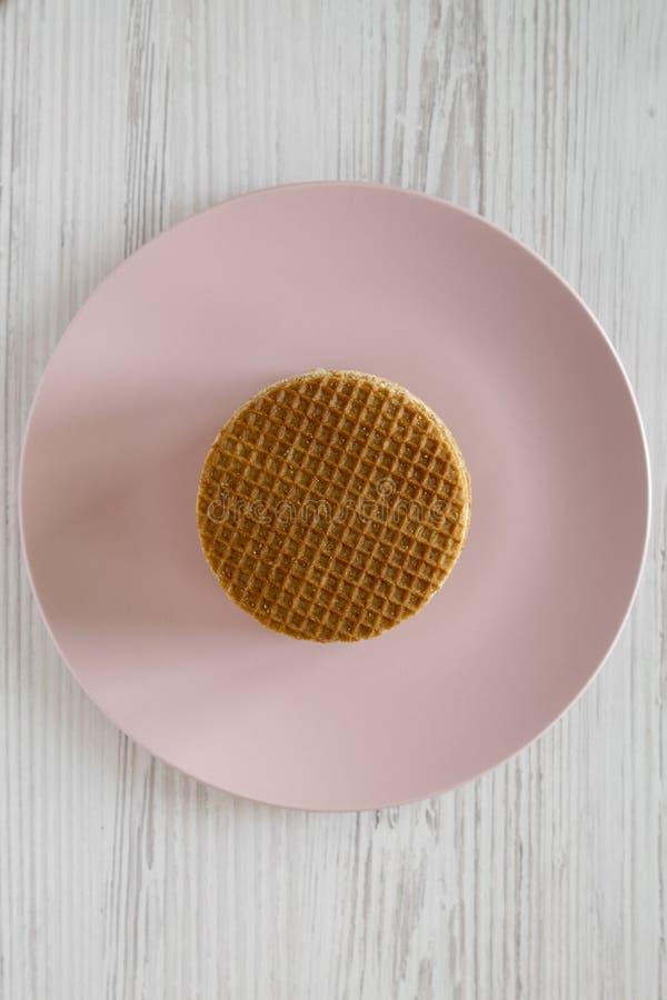 Pila de stroopwafels holandeses hechos en casa con el relleno en una placa rosada, visión superior del miel-caramelo Endecha plan fotos de archivo libres de regalías