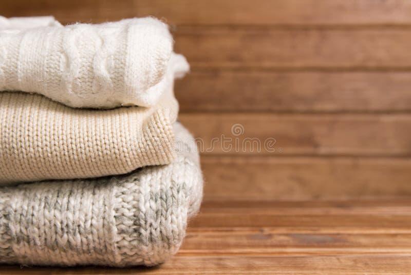 Pila de suéter caliente hecho punto acogedor, fondo de madera Suéteres blancos en estilo retro fotos de archivo libres de regalías