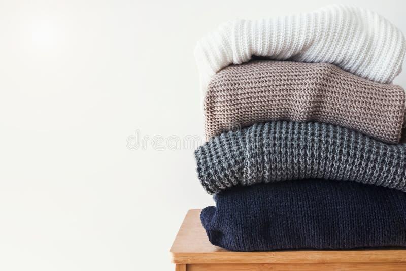 Pila de suéteres acogedores del invierno en el fondo blanco de la pared imagen de archivo