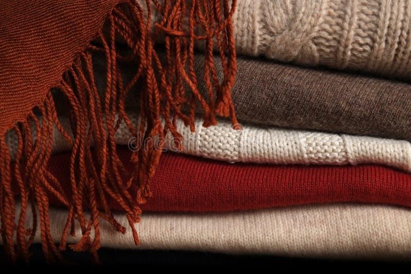 Pila de suéteres de lana y de una bufanda foto de archivo libre de regalías
