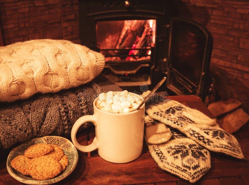 Pila de suéteres hechos punto acogedores, de manoplas hechas a mano y de taza de café, cacao, chocolate caliente con las melcocha foto de archivo