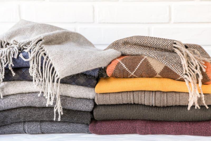 Pila de suéteres hechos punto acogedores que preparan la ropa caliente para el concepto de las estaciones del invierno del otoño fotografía de archivo libre de regalías