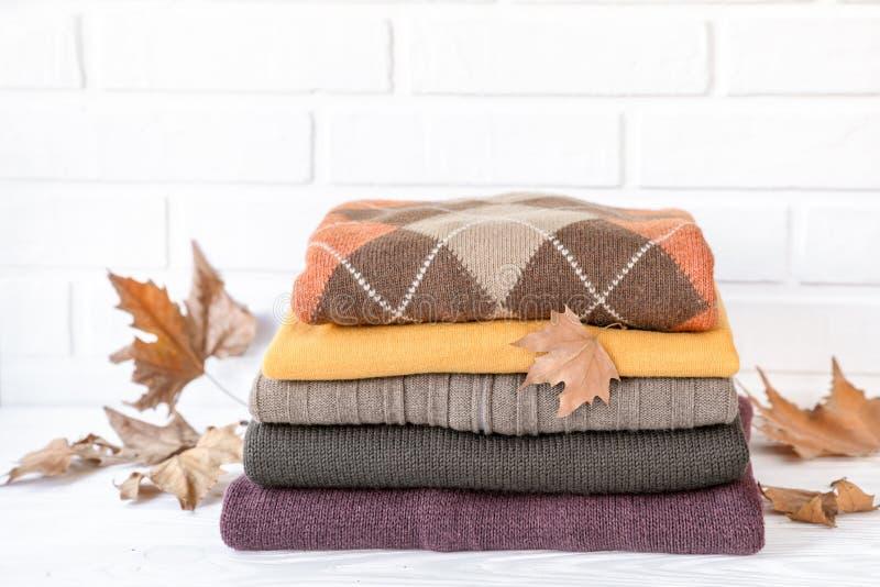 Pila de suéteres hechos punto acogedores y de hojas de arce caidas que preparan la ropa caliente para el concepto del otoño foto de archivo