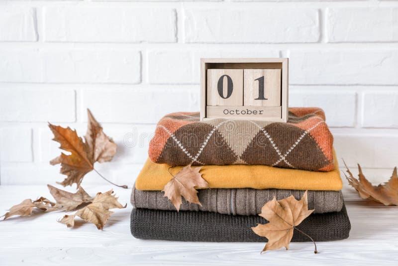 Pila de suéteres hechos punto acogedores y de hojas de arce caidas que preparan la ropa caliente para el concepto del otoño fotos de archivo libres de regalías