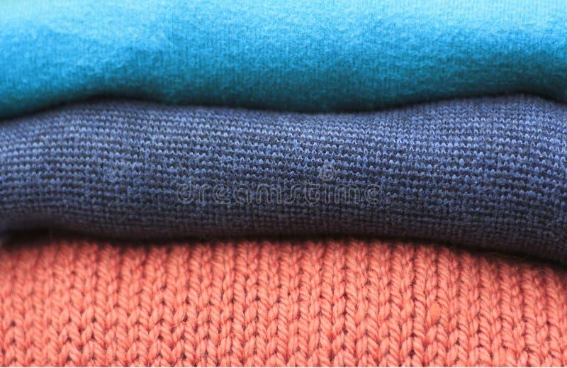 Pila de suéteres hechos punto de lana multicolores primer, textura, fondo imágenes de archivo libres de regalías