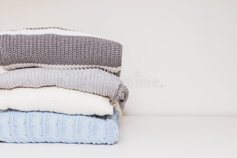 Pila de suéteres hechos punto lavados limpios acogedores cómodos acogedores en colores en colores pastel, lavadero y concepto de  foto de archivo libre de regalías