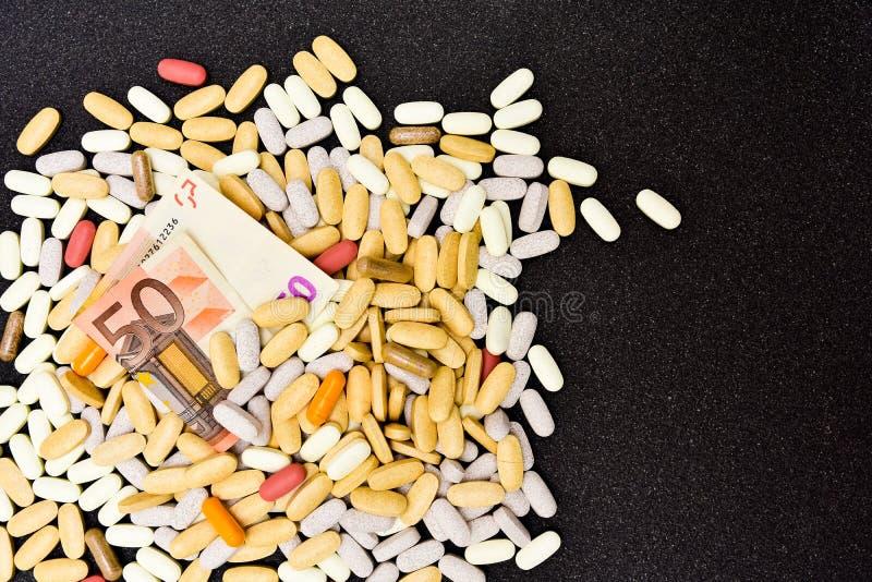 Pila de suplementos de la vitamina, minerales y herbarios con una cuenta del euro cincuenta imagen de archivo libre de regalías