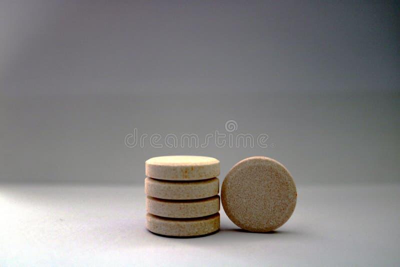 Pila de tabletas efervescentes farmacéuticas con sabor a naranja con el fondo blanco foto de archivo libre de regalías