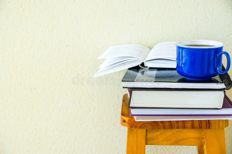 Pila de taza azul de los libros de trabajo de las libretas de los libros de texto de té caliente en alto taburete de madera en el foto de archivo