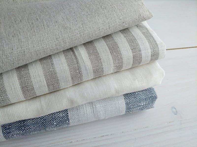 Pila de telas de algodón de lino azules grises blancas rayadas en el fondo blanco fotos de archivo