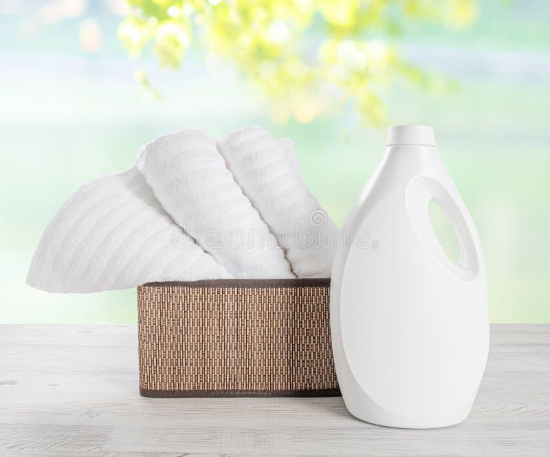 Pila de toallas blancas en el bascket y la botella vacía blanca de gel del lavadero Pila de toallas suaves limpias contra el colo fotografía de archivo libre de regalías