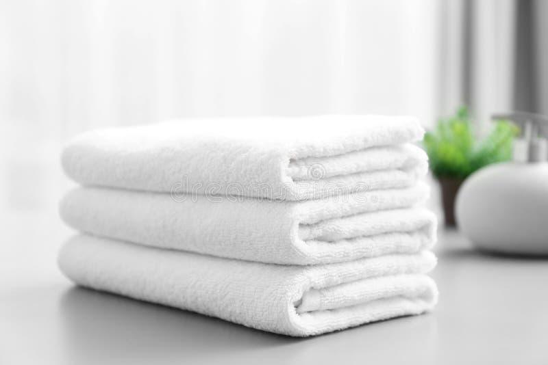 Pila de toallas limpias blancas en la tabla imagen de archivo