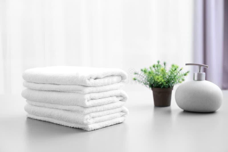 Pila de toallas limpias blancas en la tabla imagen de archivo libre de regalías
