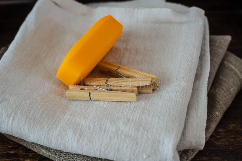 Pila de toallas de lino limpias, de pinzas y de jab?n natural en la tabla foto de archivo