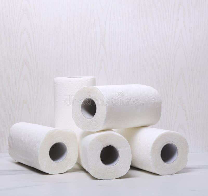 Pila de toallas de papel en la superficie de mármol blanca contra la pared de madera blanca imagenes de archivo
