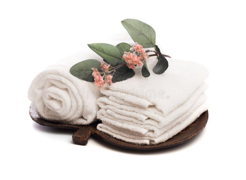 Pila de toallas suaves blancas limpias con la flor en el fondo blanco - imagen fotografía de archivo