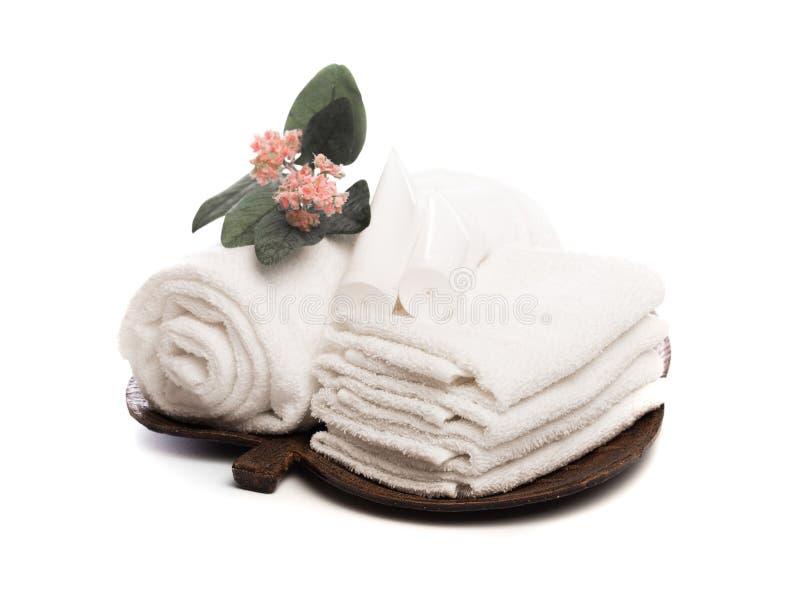 Pila de toallas suaves blancas limpias con la flor en el fondo blanco - imagen foto de archivo libre de regalías