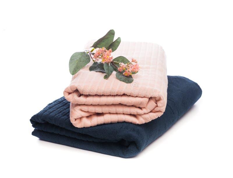 Pila de toallas suaves limpias con la flor en el fondo blanco - imagen imagenes de archivo