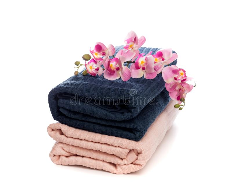 Pila de toallas suaves limpias con la flor de la orquídea en el fondo blanco - imagen imagen de archivo